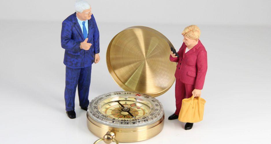 Horst Seehofer und Angela Merkel stehen als Spielfiguren neben einem Kompass